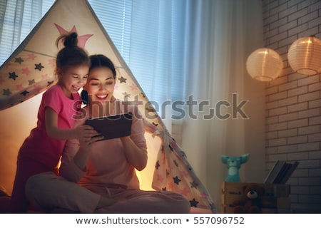 little girl with tablet pc in kids tent at home Stock photo © dolgachov
