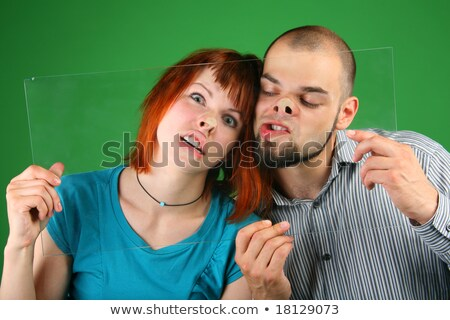 Stock photo: Close up girl with red hair and guy grimace behind glass
