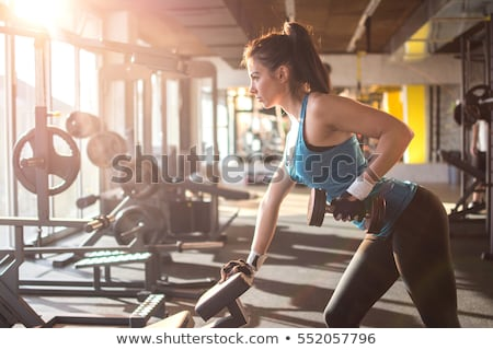 woman with weight training equipment on sport gym stock photo © lunamarina