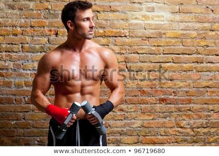 muscle shaped body man with weights on brick wall stock photo © lunamarina