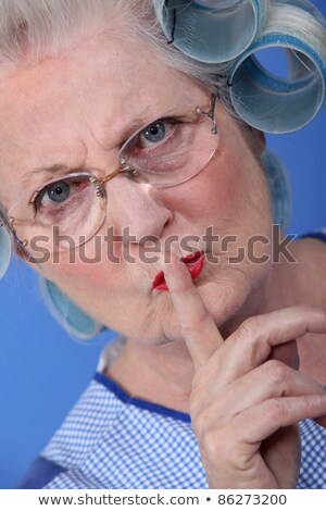 Elderly woman with her hair in rollers holding her finger up to her lips Stock photo © photography33