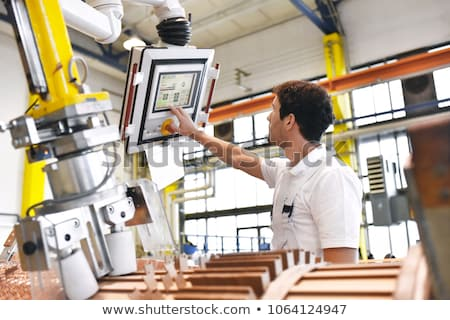 Young man operating machine in factory Stock photo © photography33