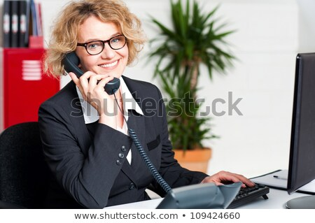 Cheerful front desk executive attending phone call Stock photo © stockyimages