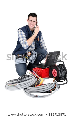 Electrician making a call whilst kneeling by his equipment Stock photo © photography33