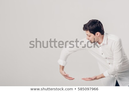 Looking for Ideas concept. Young business man standing on gray b Stock photo © HASLOO