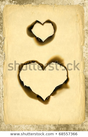 Heart shaped burned hole in paper. Stock photo © snyfer