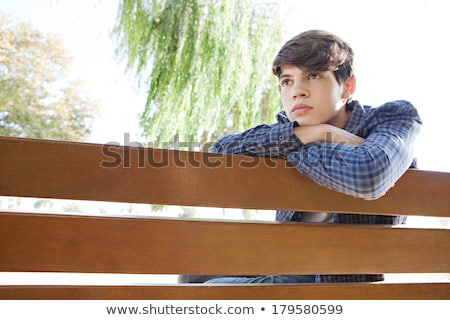 fashion man looking down while leaning on a tree  Stock photo © feedough