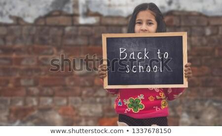 iskolás · lány · tart · iskolatábla · kicsi · gyermek · oroszlán - stock fotó © Dave_pot