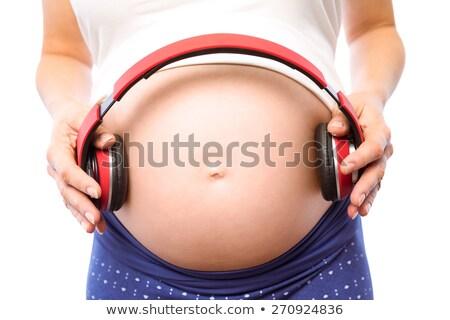 Pregnant woman holding headphones over bump Stock photo © wavebreak_media