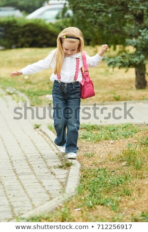 Beautiful blonde girl balancing on a curb in the city. Stock photo © nenetus