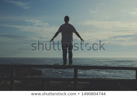 boy teenager open arms rear view looking blue sea stock photo © lunamarina