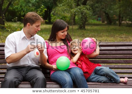 Parents together with daughter on bench in park in afternoon. Play with multi-coloured balloons. Stock photo © Paha_L