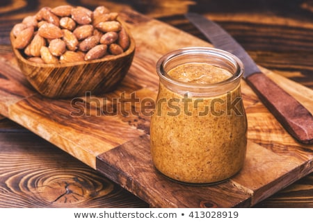 Bowl of fresh raw almonds on an old wooden board Stock photo © ozgur