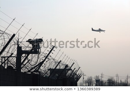 Stock photo: Airplane flying over CCTV cameras