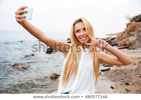 Smiling young blonde woman showing v sign while standing outdoors Stock photo © deandrobot