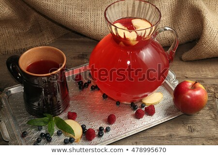 Stock photo: Fruit compot in glass jug and ceramic cup on tray.