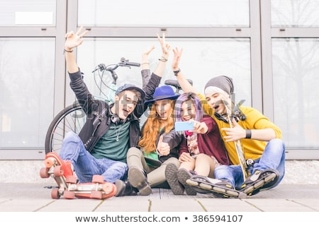 hipster sitting on the floor and having fun stock photo © deandrobot
