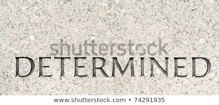 Word 'Determined' Carved in Gray Granite Stone stock photo © Qingwa
