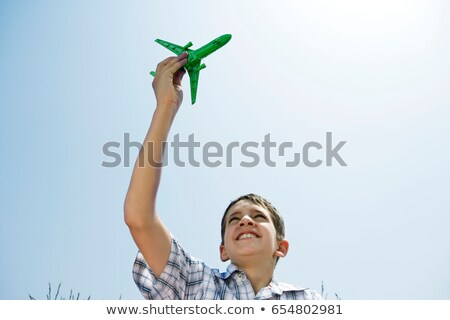 Boy holding toy plane aloft Stock photo © IS2