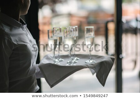Hand holds tray with pink rose champagne glasses stock photo © DenisMArt