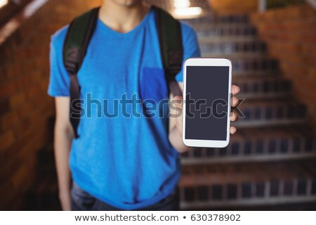Schoolboy standing with schoolbag showing mobile phone near staircase at school Stock photo © wavebreak_media