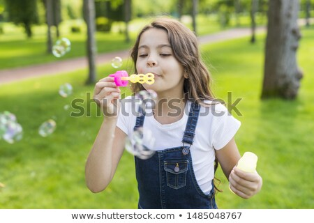 Stock photo: Little girl making soap bubbles