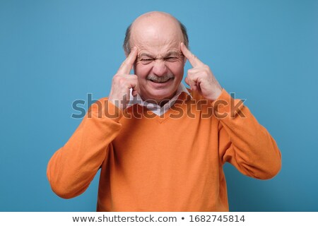Concentrating businessman holding fingers on temples Stock photo © ichiosea