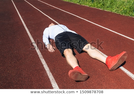 Exhausted sportsman finished running at the stadium Stock photo © deandrobot
