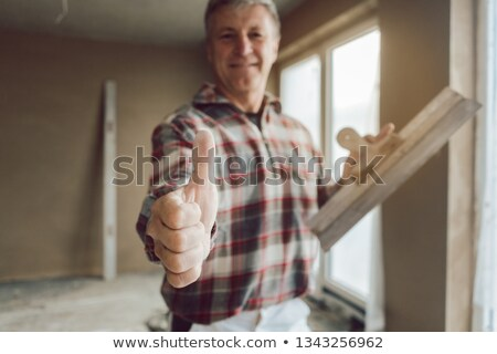 Plasterer giving thumbs-up in the interior of newly constructed house Stock photo © Kzenon