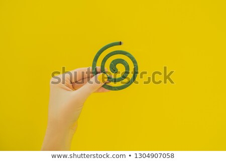Burning mosquito coil is an anti-mosquito repellent on yellow background in hand with yellow manicur Foto d'archivio © galitskaya