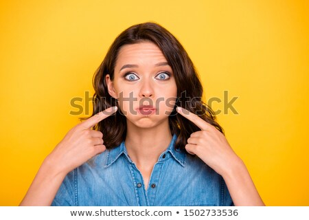 Foto d'archivio: Young woman blowing her cheek