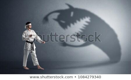 Karate man fighting with a big scary shadow Foto stock © ra2studio