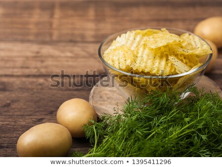 Homemade potato crisp chips inside glass bowl with fresh raw dill on wooden background and raw potat Stock photo © DenisMArt