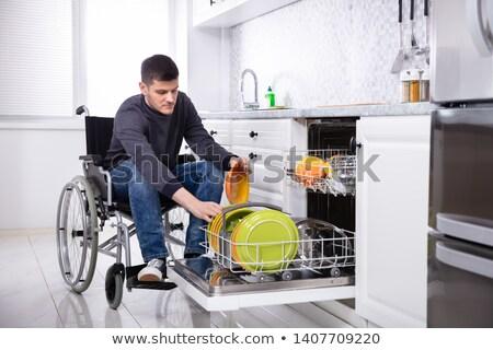 Fogyatékos férfi tányérok mosogatógép fiatal ül Stock fotó © AndreyPopov