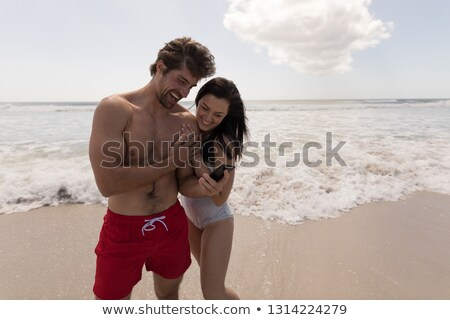 Front view of happy young couple using mobile phone and having fun at beach in the sunshine Stock photo © wavebreak_media