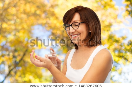 smiling senior woman spraying perfume to her wrist Stock photo © dolgachov