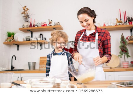 Happy young mother whisking raw eggs in bowl with her little son near by Stock photo © pressmaster