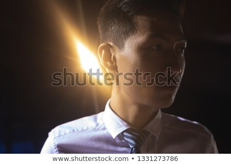 Close-up of young Asian businessman standing on stage in auditorium. Businessman thinking  Stock photo © wavebreak_media
