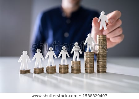 Human Hand Placing Human Figure On Increasing Stacked Coins Stock photo © AndreyPopov