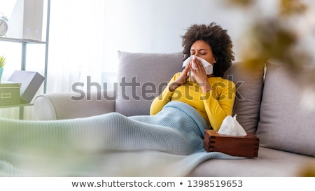 sick woman blowing nose in paper tissue at home Stock photo © dolgachov