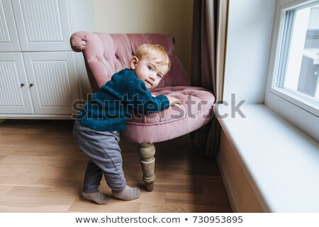 Small blonde child leans at armchair, plays alone at home. Little infant teaches to go. Adorable kid Stock photo © vkstudio