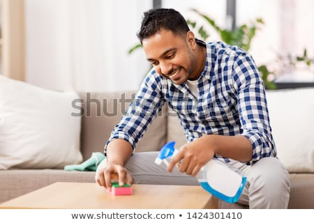 indian man cleaning table with detergent at home Stock photo © dolgachov