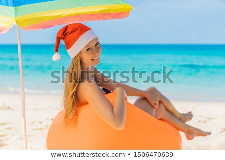 Kobieta nadmuchiwane plaży kanapie christmas hat Zdjęcia stock © galitskaya