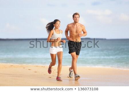 Couple athletes runners running on beach. Interracial young adults asian woman, caucasian man, train Stock photo © Maridav