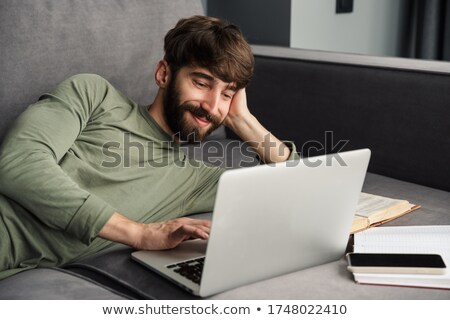 Image of concentrated young man using laptop while lying on sofa Stock photo © deandrobot