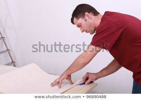 Tradesman cutting a sheet of paper Stock photo © photography33