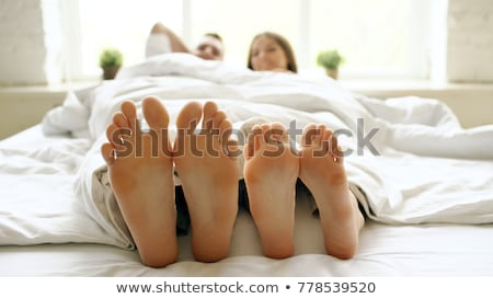 close up of couples feet while having fun in their bed at home stock photo © wavebreak_media