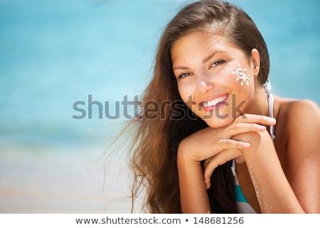 brunette at beach applying suncream stock photo © photography33