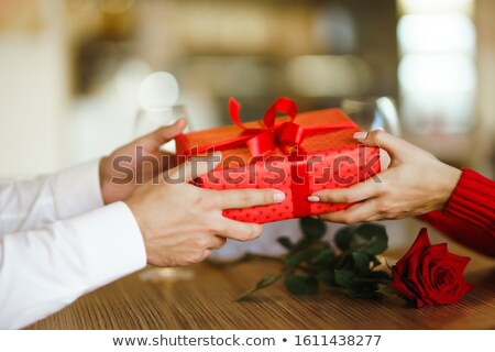 man giving christmas gift to his woman in restaurant stock photo © hasloo