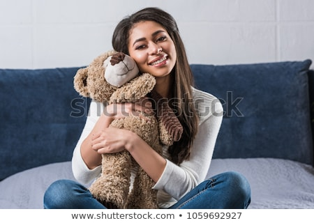 Young happy woman sitting on the bed with teddy bear Stock photo © deandrobot